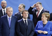 In this Sunday, Jan. 19, 2020 file photo, German Chancellor Angela Merkel, front right, speaks with French President Emmanuel Macron, front center, and Turkish President Recep Tayyip Erdogan during a group photo at a conference on Libya at the chancellery in Berlin, Germany.(AP Photo/Michael Sohn, File)