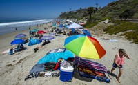 Umbrellas, blankets and towels are socially distanced in San Clemente, Calif. on July 4, 2020. (Mark Rightmire/The Orange County Register via AP)