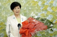 In this image made from YouTube provided by Koike Yuriko Official Channel, Tokyo Gov. Koike recieves a bunch of flower from supporter during her gubernatorial election victory press conference at her election office in Tokyo, on July 5, 2020. (Koike Yuriko Official Channel via AP)
