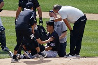 New York Yankees pitcher Masahiro Tanaka is tended to by team medical personnel after being hit by a ball off the bat of Yankees Giancarlo Stanton during a baseball a workout at Yankee Stadium in New York, on July 4, 2020. (AP Photo/Adam Hunger)