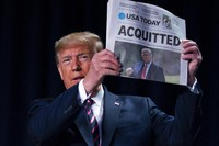 In this Feb. 6, 2020, file photo, President Donald Trump holds up a newspaper with the headline that reads