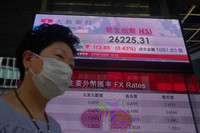 A woman wearing a face mask walks past a bank's electronic board showing the Hong Kong share index at Hong Kong Stock Exchange on July 7, 2020. (AP Photo/Vincent Yu)