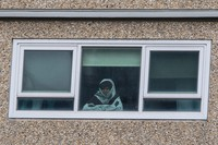 A woman looks out a window from a locked-down public housing tower in Melbourne, on July 6, 2020. (AP Photo/Andy Brownbill)