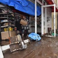 泥だらけになった店舗を片付ける女性。道路には横転した車や流木が残る=大分県日田市天瀬町で2020年7月8日午前8時47分、田鍋公也撮影