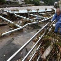 玖珠川の氾濫で崩落した橋のたもとで片付けをする住民=日田市天瀬町で2020年7月8日午前10時18分、田鍋公也撮影
