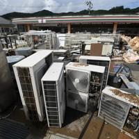 コンビニエンスストアの駐車場に置かれた大量の災害ゴミ=熊本県芦北町で2020年7月8日午前9時43分、矢頭智剛撮影