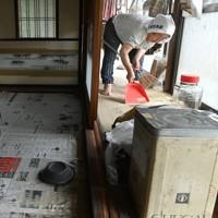 浸水し自宅にたまった泥を掃除する久保田敏子さん(86)。1972年の水害後に自宅を1メートル以上かさ上げしたが、今回はさらに床上30センチほどまで浸水し「こげなことは初めて。たまがった」。夜は八代市の中心部に住む息子宅に身を寄せ、昼間に自宅を片付けに帰ってきている=熊本県八代市坂本町で2020年7月8日午後4時45分、徳野仁子撮影