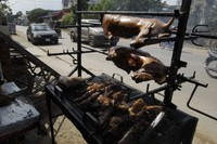 In this Mar. 30, 2017 file photo, a local vendor grills dog meat on the sidewalk on the outskirts of Phnom Penh, Cambodia. (AP Photo/Heng Sinith)