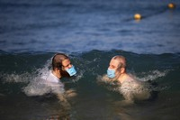 Ultra-orthodox Jewish men wearing protective face masks swim in the Mediterranean Sea, on a beach reserved for males three days a week, in Tel Aviv, Israel, on July 8, 2020.  (AP Photo/Oded Balilty)
