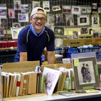 唐桑体育館で大量に保管する被災した写真を前に笑顔を見せるイチゴ農家の男性。市の委託を受け、回収された写真の返還責任者になった=宮城県気仙沼市で2011年7月15日、梅村直承撮影