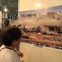 ブラジル・サンパウロで東日本大震災の写真展が開催され、毎日新聞写真部の手塚耕一郎記者が撮影した、津波が押し寄せる瞬間の写真に見入る女性=サンパウロ市内で2011年7月15日、朴鐘珠撮影