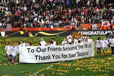 サッカー女子W杯ドイツ大会で優勝し、東日本大震災の被災者への世界からの支援に対して謝意を示す横断幕を掲げ、場内を一周するなでしこジャパンの選手たち=ドイツ・フランクフルトで2011年7月17日、篠田航一撮影