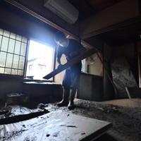 泥まみれになった客室を片付ける旅館「一富士」代表の松田諭さん=熊本県人吉市で2020年7月9日午前10時18分、宮間俊樹撮影