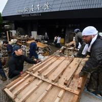 浸水被害のあった老舗温泉旅館「鍋屋本館」で片付けをする関係者ら=熊本県人吉市で2020年7月9日午前9時34分、宮間俊樹撮影