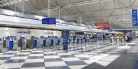 Rows of United Airlines check-in counters at O'Hare International Airport in Chicago are unoccupied on June 25, 2020, amid the coronavirus pandemic. United is sending layoff warnings to 36,000 employees, nearly half its U.S. staff, the airline announced on July 8. (AP Photo/Teresa Crawford)