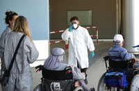Medical staffers check passengers arriving at Rome's Leonardo Da Vinci international airport, on July 8, 2020. Rome airport authorities have refused to let 112 Bangladeshi passengers off a plane that landed from Qatar as Italy tightens restrictions on people arriving from coronavirus hotspots. (Mauro Scrobogna/LaPresse via AP)