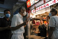 Singapore Prime Minister and Secretary-General of the People's Action Party Lee Hsien Loong, second left, wears a face mask while talking to food vendors at a local market at Yio Chu Kang while on the campaign trail in Singapore July 3, 2020. (AP Photo/Ee Ming Toh)