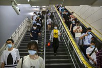 Commuters wearing face masks to protect against the spread of the new coronavirus walk through a subway station in Beijing, on July 9, 2020. (AP Photo/Mark Schiefelbein)