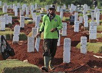 A worker walks among graves at a special cemetery for people who presumably died of COVID-19 in Jakarta, Indonesia, on June 12, 2020. (AP Photo/Achmad Ibrahim)