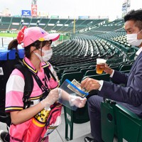 【阪神―DeNA】マスクに手袋を着用して現金はビニール袋入れる方法で販売するビールの売り子=兵庫県西宮市の阪神甲子園球場で2020年7月10日(代表撮影)