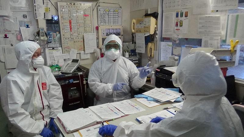 防護服やゴーグルを着用し、回診前の打ち合わせをする富山大病院の山城清二教授(中央)ら=富山市の富山リハビリテーションホームで2020年5月4日、山城教授提供