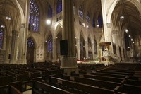 In this April 12, 2020 file photo, Archbishop Timothy Dolan, right, delivers his homily over mostly empty pews as he leads an Easter Mass at St. Patrick's Cathedral in New York. (AP Photo/Seth Wenig)
