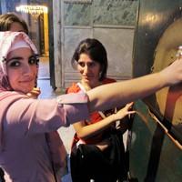 アヤソフィアにある「マリアの手形」。親指を入れて1回転すると願いがかなうといわれ、笑顔で試すトルコの高校生=トルコ・イスタンブールで2012年4月23日、手塚耕一郎撮影