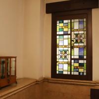 階段にはショーウインドーに使われていたステンドグラス(右)が移され、天秤も展示されている=大阪市中央区で2020年5月22日、大西達也撮影