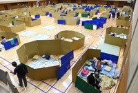 Evacuees at a school gym serving as an evacuation center in the city of Yatsushiro, Kumamoto Prefecture, are seen split by partitions made of cardboard on July 7, 2020. (Mainichi/Noriko Tokuno)