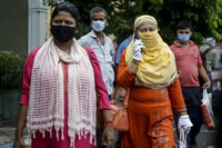 Commuters with face mask as a precaution against the coronavirus wait for a bus in Kolkata, India, on July 9, 2020. (AP Photo/Bikas Das)
