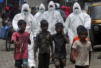 Health workers wearing protective clothing arrive to screen people for COVID-19 symptoms at a slum in Mumbai, India, on July 10, 2020. (AP Photo/Rafiq Maqbool)