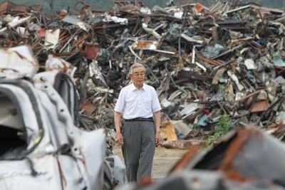 震災のがれきの前に立つ男性。戦後の焼け跡を、釜石で鉄とともに歩んできた=岩手県釜石市で2011年7月25日、後藤由耶撮影