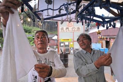 住民の署名で継続が決まった「復興の湯」を運営する人たち=岩手県陸前高田市で2011年7月27日、宮間俊樹撮影
