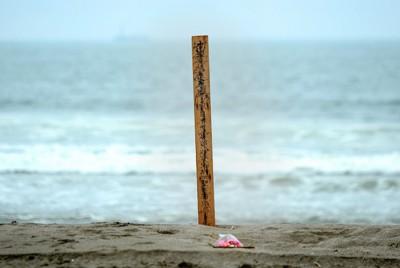 がれきとみられる板で作られた卒塔婆が無人の海水浴場に立つ。そばには花が手向けられていた=宮城県東松島市で2011年7月28日、津村豊和撮影