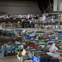 ひとりの女性が始めた写真の整理は、他のボランティアに引き継がれ、震災から4カ月が過ぎても続いていた=宮城県名取市の閖上中体育館で2011年7月31日午後12時0分、金森崇之撮影