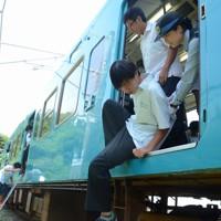 津波発生を想定した避難訓練で、緊急停車した電車から避難する高校生=和歌山県新宮市で2017年7月31日午前10時56分、石川裕士撮影