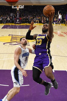 In this Jan. 15, 2020, file photo, Los Angeles Lakers forward LeBron James, right, shoots as Orlando Magic center Nikola Vucevic defends during the second half of an NBA basketball game, in Los Angeles.(AP Photo/Mark J. Terrill, File)