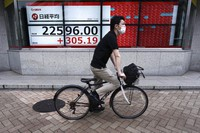 A man wearing a face mask to help curb the spread of the coronavirus rides a bicycle near an electronic stock board showing Japan's Nikkei 225 index at a securities firm in Tokyo on July 13, 2020. (AP Photo/Eugene Hoshiko)