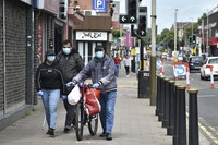 People wearing masks to protect against coronavirus, walk in Melton Road also known as the Golden Mile in Leicester, England, on June 30, 2020. (AP Photo/Rui Vieira)