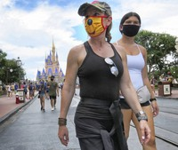 Guests wear masks as required to attend the official reopening day of the Magic Kingdom at Walt Disney World in Lake Buena Vista, Fla., on July 11, 2020. (Joe Burbank/Orlando Sentinel via AP)