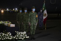Mexican soldiers mourn five boxed cremated remains, of Mexicans who died from COVID-19, during a welcoming ceremony at the tarmac of Benito Suarez International airport in Mexico City, on July 11, 2020. The ashes of 245 Mexican were repatriated to Mexico from New York in a military airplane. (AP Photo/Fernando Llano)