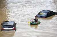 In this photo released by Xinhua News Agency, a man paddles with an inflatable boat past submerged cars during a flood in Rongshui County in southern China's Guangxi Zhuang Autonomous Region, on July 11, 2020. (Long Linzhi/Xinhua via AP)