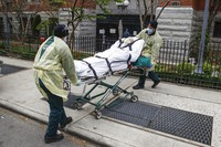 In this April 17, 2020, file photo, a patient is prepared to be loaded into the back of an ambulance by emergency medical workers outside Cobble Hill Health Center in the Brooklyn borough of New York. (AP Photo/John Minchillo)