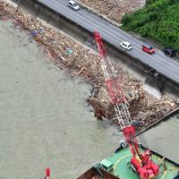 宇城市の沿岸部に漂着した流木などを回収する作業船=熊本県宇城市沖で2020年7月14日、本社ヘリから須賀川理撮影