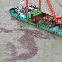 漂流する流木などをクレーンで回収する船=熊本県宇城市沖でで2020年7月14日午後2時37分、本社ヘリから須賀川理撮影