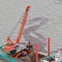 漂流する流木などをクレーンで回収する船=熊本県宇城市沖でで2020年7月14日午後2時38分、本社ヘリから須賀川理撮影