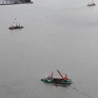 漂流する流木などをクレーンで回収する船=熊本県宇城市沖でで2020年7月14日午後3時16分、本社ヘリから須賀川理撮影
