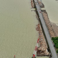 宇城市の沿岸部に漂着した木などをクレーンで回収する船=熊本県宇城市沖でで2020年7月14日午後2時34分、本社ヘリから須賀川理撮影