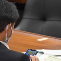 衆院東日本大震災復興特別委員会中にスマートフォンを閲覧する山崎誠議員。この後、健康商品の無料モニター登録を始めた=2020年5月19日、大場弘行撮影