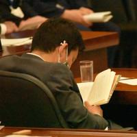 衆院沖縄及び北方問題に関する特別委員会中に「女帝 小池百合子」を約2時間読んだ井野俊郎議員。途中、ページを開いたまま同じ姿勢をとり続けた=2020年6月18日、大場弘行撮影
